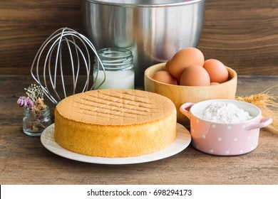 Homemade delicious sponge cake or soft cake on white plate with ingredients: eggs flour milk put on wood table with copy space. Bakery concept for background or wallpaper.