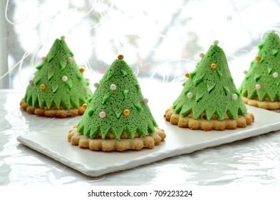 Homemade dessert Christmas tree made of Japanese sponge cake, cream and shortbread. selective focus.