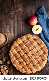 Homemade dessert, old fashioned lattice crust pie with grated apple and walnut filling, sprinkled with granulated sugar and cinnamon on a rustic wooden background with copy space