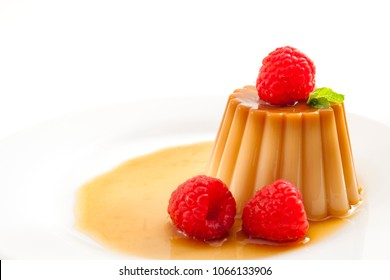 Homemade dessert and smooth custard sweets concept with close up on creme caramel, flan, or caramel pudding covered in sweet syrup and raspberries isolated on white background with copy space