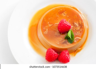 Homemade dessert and smooth custard sweets concept with top view of creme caramel, flan, or caramel pudding covered in sweet syrup and raspberries isolated on white background with copy space