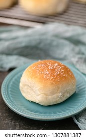 Homemade Dinner Roll on Turquoise Plate with Additional Rolls on Wire Rack in Background