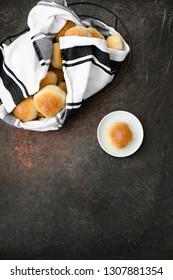 Homemade Dinner Roll on White Plate; Basket of Dinner Rolls in Background