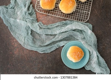 Homemade Dinner Rolls on Wire Rack; One Isolated on a Turquoise Plate