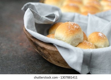 Homemade Dinner Rolls in Wooden Bowl with Gray Napkin; Additional Rolls in Background