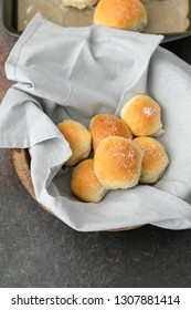 Homemade Dinner Rolls in a Wooden Bowl with Gray Napkin; Additional Rolls in Pan in Background