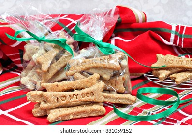 Homemade dog bone biscuits stamped with I Love My Dog being packaged as healthy Christmas gifts in cellophane bags.