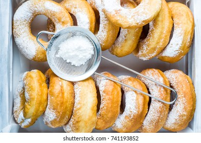 Homemade donuts with powdered sugar in a white wooden box