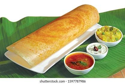 Homemade Dosa, dhosa, masala, plain, maisuri (Ghee Roast) with Chutney and Sambar on banana leaf isolated South Indian Breakfast Thali