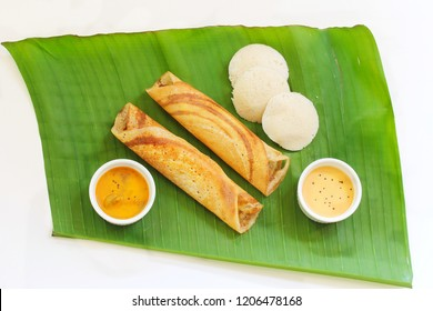 Homemade Dosa (Ghee Roast) and Idli with Chutney and Sambar on banana leaf isolated on white, top view/ South Indian Breakfast Thali
