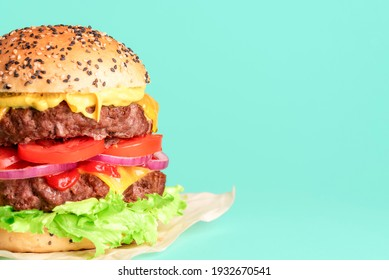 Homemade double burger with cheese, vegetables and sauces isolated on a green background. Delicious cheeseburger on wax paper