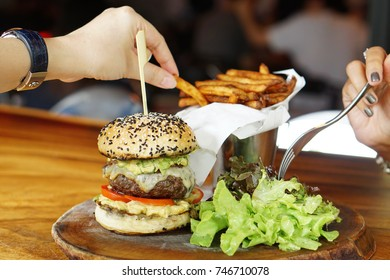Homemade double cheese burger assorted with wagyu beef, tomato, onion, cheddar cheese, lettuce, spicy sauce served with french fries and salad on blurred background.