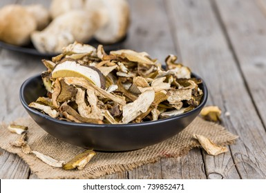 Homemade Dried Porcinis on an wooden table as detailed close-up shot; selective focus