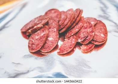 home-made dry-cured sausage in a polymer shell on a foil background