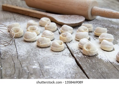 Homemade dumplings with flour and kitchenware on rustic wooden background. Traditional russian pelmeni. Semi-finished products.