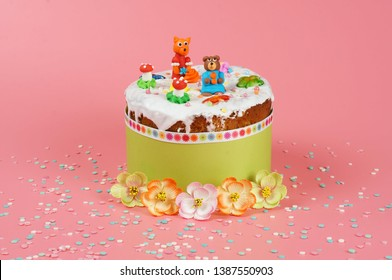 Homemade easter loaf with white coating and figures of fox, bear, mushrooms and flowers in green wrap. Pink background with sprinkles. Decorated by paper flowers