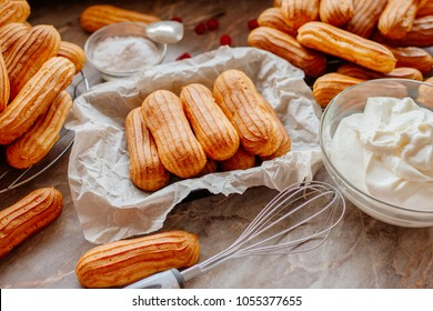 Homemade eclairs. Preparation of eclairs in the home kitchen. The process of cooking eclairs.Eclair a small, soft, log-shaped pastry filled with cream and typically topped with chocolate icing.