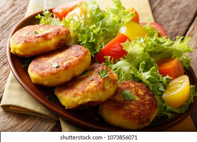 Homemade Ecuadorian potato pancakes with fresh vegetable salad close-up on a plate on a table. Llapingachos. horizontal