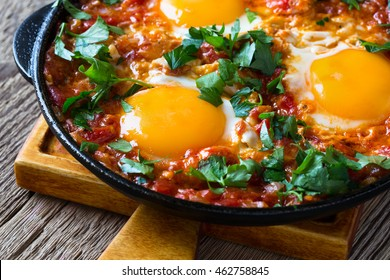 Homemade egg dish with tomato sauce  served in  cast iron pan, shakshouka, comfort food
