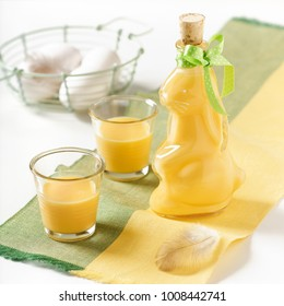 Homemade egg liquour in a rabbit shaped bottle with two glasses. Square image.
