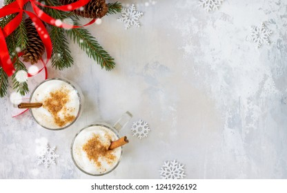 Homemade Eggnog Christmas milkshake with cinnamon, served in two cups on a stone or slate background, decorative ornaments, Christmas tree. Top view with copy space.