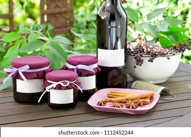 Homemade elderberry jelly and juice in a bottle and glass jars with elderberries on a wooden table outdoors in front of green leaves, copy space