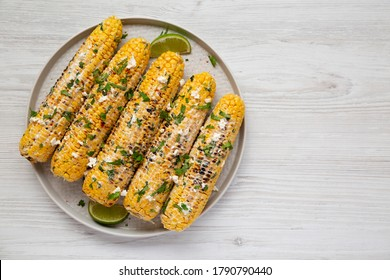 Homemade Elote Mexican Street Corn on a plate on a white wooden background, top view. Copy space.