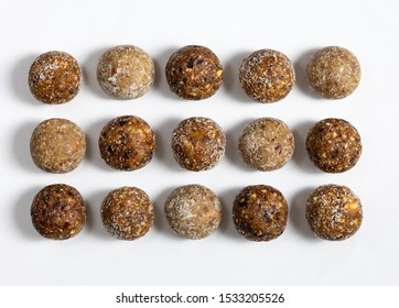 Homemade energy balls with dried apricots, raisins, dates, prunes, walnuts, almonds and coconut. Healthy sweet food. Energy balls on a white background. Flat lay, top view.