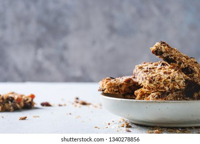 Homemade energy oats granola bars with dried fruits and nuts whole and broken in ceramic plate on grey table. Healthy snack.