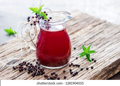 Homemade essence of elderberry berries in jars and bottles in front of a vintage board on wood