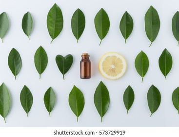 Homemade essential oil concept. bottle essential oil with slice lemon, leaf in heart shape on white wooden table background from top view