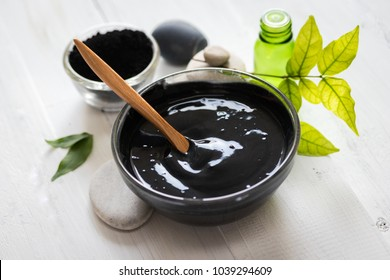 Homemade facial mask and scrub by activated charcola powder and yogurt on white wooden background