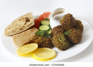 Homemade falafels (herbed and spicy chickpea balls) on a plate with Egyptian flat bread, lemon slices, tomato, cucumber and a tahina sauce.