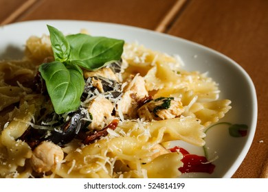 Homemade farfalle pasta with chicken, black olives, dried tomato, parmesan cheese and basil.
