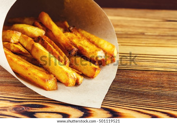 Homemade fast food portion of french fries in paper bag on wood table, selective focus