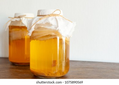 """homemade fermented drink Jun Tea SCOBY """"symbiotic culture of bacteria and yeast"""" in a glass jar."""