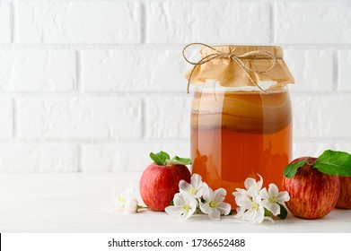 Homemade fermented kombucha in a glass jar and red apples on a background of a white brick wall. Kombucha SCOBY Symbiotic culture of bacteria and yeast. Horizontal orientation with copy space.