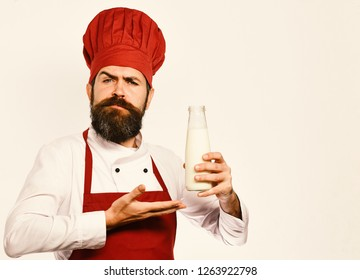 Homemade food concept. Cook with proud face in burgundy uniform has liter of fresh milk. Chef with milkshake or yoghurt. Man with beard presents bottle of milk on white background.