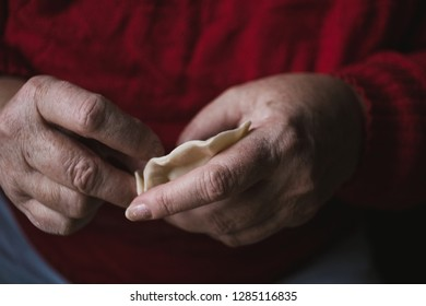 Homemade food - hands of a woman making traditional Polish pierogi. Soft moody tones.