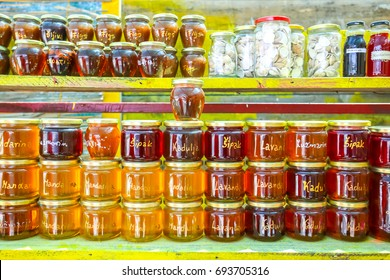 Homemade food products, honey of several plants, lavender, rosemary, pomegranate, sage and mandarin and jam of several types of fruit, figs, mandarin and plum displayed at a food stand.