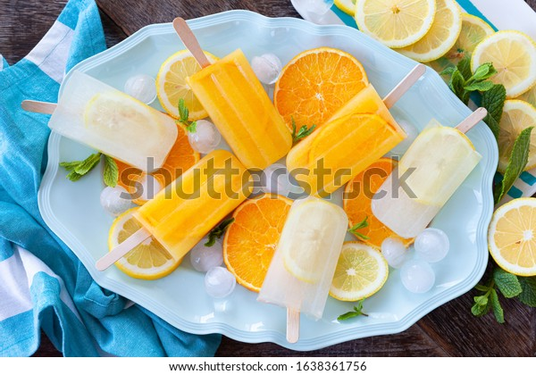 Homemade fozen popsicles with fresh lemon and oranges