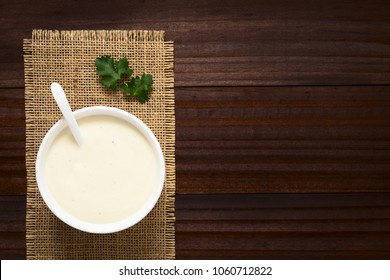Homemade French Bechamel or White Sauce served in sauce boat, photographed overhead on dark wood with natural light (Selective Focus, Focus on the sauce)