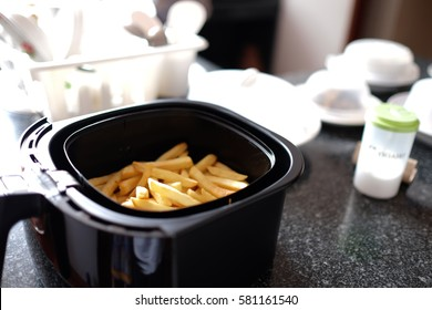 Home-made french fries in modern airfryer, DIY home food concept
