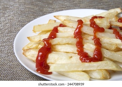 Homemade french fries on a white plate with ketchup squirted on top. An inexpensive alternative to fast food restaurants.