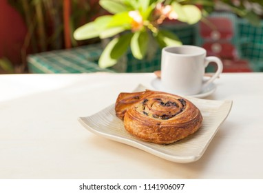 Homemade French spiral Chocolate danish with hot coffee on wooden table over blurred garden and pool background, morning outdoor day light, breakfast concept