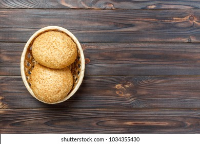 Homemade fresh buns in a basket on old wooden table.