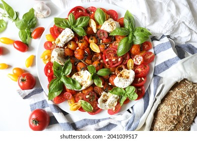 Homemade fresh healthy caprese salad with fresh variety of tomatoes and roasted cherry tomatoes, basil leaves and mozzarella Fresca cheese seasoned with balsamic vinegar and pine nuts. Copy space