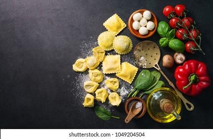 Homemade fresh Italian ravioli pasta on dark background, top view