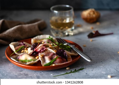 Homemade fresh ravioli with beetroot and ricotta with a glass of white wine on a grey background. Selective focus