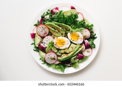 Homemade Fresh spring salad with rucola, radish with red onion and avocado with eggs in white bowl on chalkboard background with free text space. healthy winter vegetarian food. Top view.